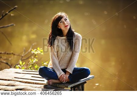 Young Woman Sitting On The Old Bridge Barefoot. Summer, Green Forest, Lake And Air In The Evening Br