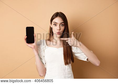 Excited Woman Showing News On Screen, Pointing At Empty Phone And Looking Surprised, Standing On Bei
