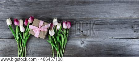 Overhead View Of Pink Tulips Surrounding A Giftbox On Rustic Wood For Mothers Day Concept