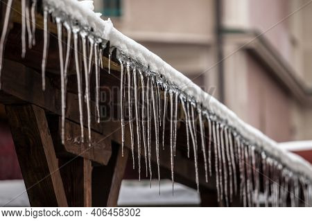 Icicles Forming Ice Stalactites Falling Fron The Edge Of The Eaves Of Gutters And Roofs Of A Residen