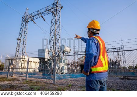 Electric Engineer Wear A Helmet Check The Transmission Station, Concept Of Electric Power Safety.