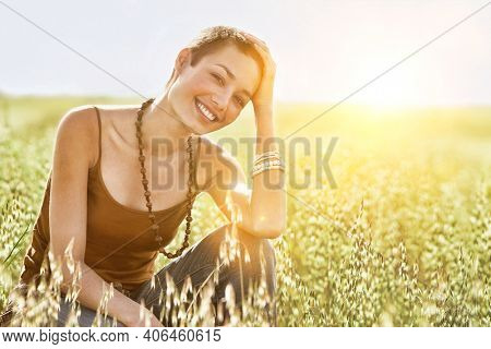 Portrait of young woman crouching in field of grass
