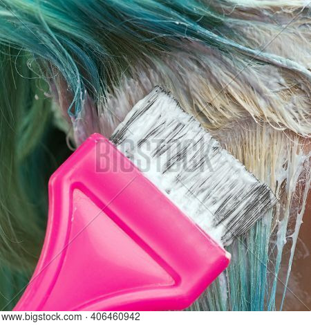 Close-up Of Hairdresser Use Pink Brush While Applying Paint To Female Client With Emerald Hair Color