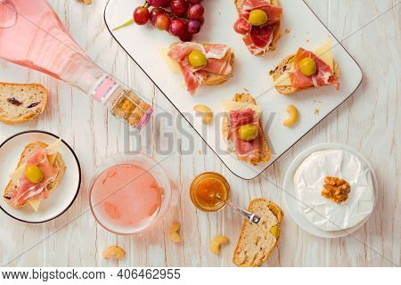 Flat lay of  Appetizers and open sandwiches with Italian antipasti, camembert, Parma ham and rose wine on wooden table