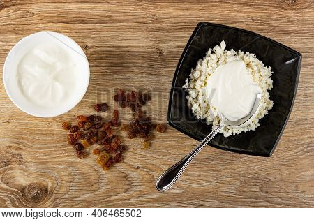 White Bowl With Sour Cream, Scattered Raisin, Spoon In Black Glass Bowl With Defatted Grainy Cottage