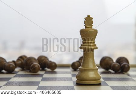 White Chess King Among Lying Down Black Pawns On Chessboard. Concept: Leader And Competition