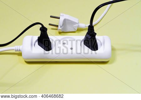 White And Black Electrical Wires From The Extension Cord On A Yellow Background. Two Plugs Are Inser