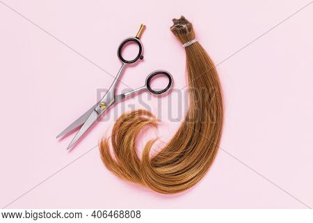 The Cut Off Strand Of Female Children's Hair Of Light Brown Color And Scissors On A Pink Background.