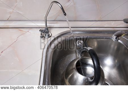 Pouring Filtered Water Into Kettle From Water Filter. Closeup Of Sink And Faucet. Drinkable Water In