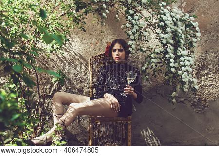 Spring Woman. Girl Or Pretty Woman, Fashionable Young Model With Wine Glass Under Blossoming Flowers