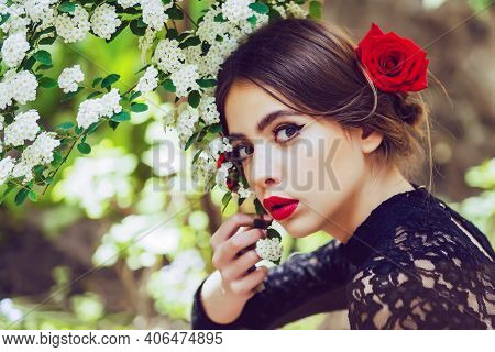 Beautiful Sensual Young Woman In Flowers In Summer Blossom Park. Cute Girl With Red Lips Posing With