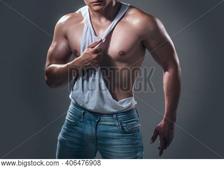 Shirtless Man. Muscular Sexy Man With Naked Torso. Man Wearing White Sleeveless Shirt On Grey Backgr