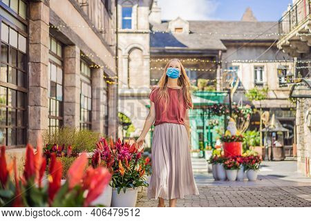 Young Woman Tourist Wearing A Medical Mask During Covid-19 Coronavirus Walks Down The Street In A Eu