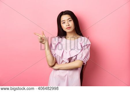 Young Smug Asian Girl Looking Cool And Pointing Finger Left At Logo, Advertising Product On Pink Rom