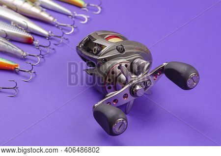Artificial Lures For Fishing For Predatory Fish And A Fishing Reel On A Blue Background. Random Wobb