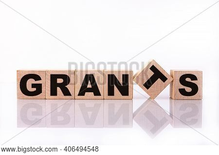 Grants Word, Text Written On Wooden Cubes On A White Background With Reflection.