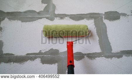 Roller And Foam Block. A Construction Roller With A Fur Nozzle On The Background Of A Wall Made Of A