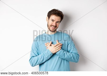 Portrait Of Young Handsome Man With Beard, Holding Hands On Heart And Saying Thank You, Thinking Abo