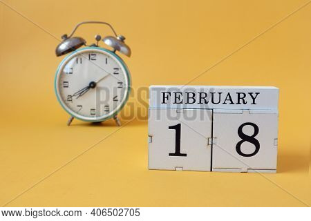 Calendar For February 18: Cubes With The Number 18 And The Name Of The Month, Alarm Clock On A Yello
