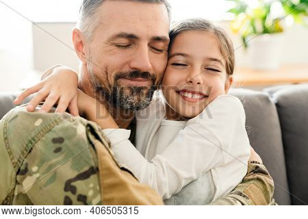 Happy military father and his daughter reunion at home. Family reunion or returning home concept