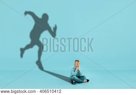 Childhood And Dream About Big And Famous Future. Conceptual Image With Boy And Shadow Of Sportive Ma