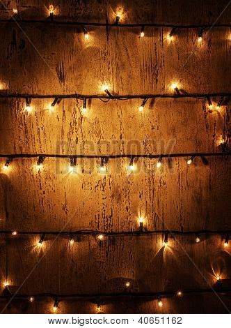 Picture of decorated door, abstract background, vintage wooded wall with glowing shining Christmas lights, decorative garland, festive electric festoon, New Year illuminated home ornament