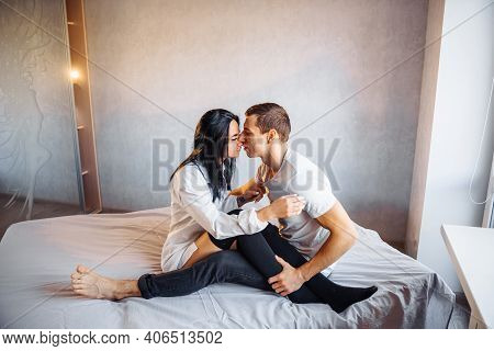 Beautiful Passionate Couple Having Sex On The Bed. Cheerful Romantic Lovers Hugging. The Boyfriend A