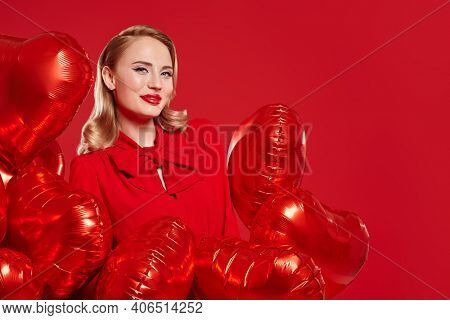 Portrait of a beautiful blonde woman in red dress posing with red heart shaped balloons on a red background. Love and Valentine's Day concept. Beauty, make-up and cosmetics. Copy space.