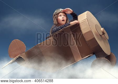 Fantasy, imagination. Cute dreamer girl playing with a cardboard airplane, purposefully looking into the distance. Childhood. Studio portrait on a blue background with clouds.