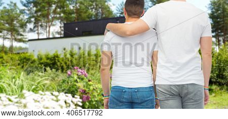 lgbt, same-sex relationships and homosexual concept - close up of hugging male couple wearing gay pride rainbow awareness wristbands over home garden on back yard background