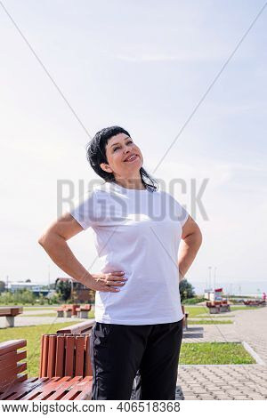 Smiling Senior Woman Doing Warm Up Before Training Outdoors In The Park