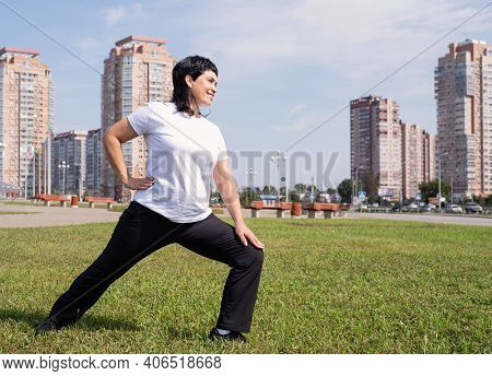 Smiling Senior Woman Warming Up Stretching Outdoors In The Park