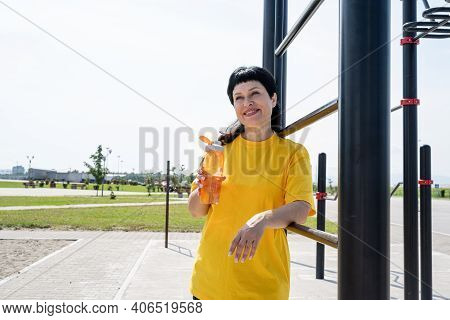 Smiling Senior Woman Drinking Water After Workout Outdoors On The Sports Ground
