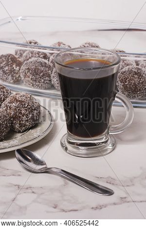 A Coffee With Oats Bonbons Dessert And A Spoon In A White Table