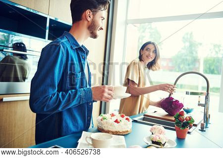 Happy young couple drink tea in the kitchen at home and talk. Home interior, furniture. Happy family concept.