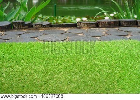 Green Soft Artificial Grass Near The Pond In A Garden. Artificial Turf Background.