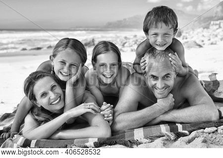 Black and white photo of happy family lying on the beach