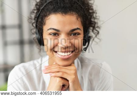 Headshot Of Friendly African American Millennial Woman In A Headset Sitting With Her Hands On A Chin