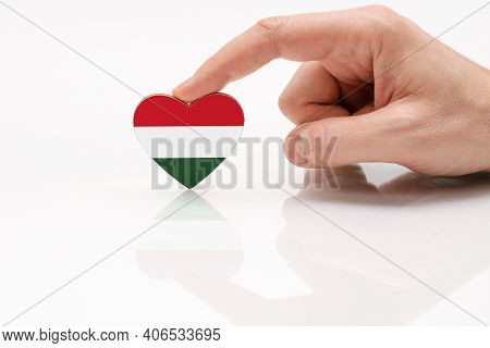 Love And Respect Hungary. A Man's Hand Holds A Heart In The Shape Of The Hungarian Flag On A White G