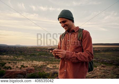 Happy Male Hiker With Backpack And Cap Using Smartphone On Mountain
