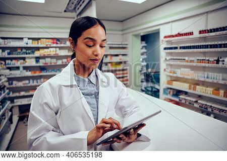 Young Female Woman Working In Pharmacy Standing Behind Counter Wearing Labcoat Using Digital Tablet