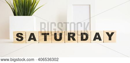 Wooden Cubes With Letters On A White Table. The Word Is Saturday. White Background With Photo Frame,