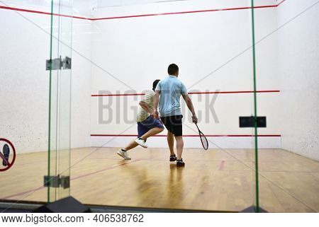 Squash Player In Action Reaching On Squash Court. Out Of Focus, Possible Granularity, Motion Blur
