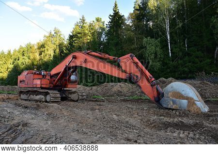 Excavator During Groundwork At Forest Area For Construction New Road. Orange Backhoe On Road Work, L