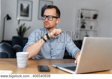 An Intelligent Young Man In Glasses And Casual Shirt Sits At The Desk With A Laptop And Looks Away L