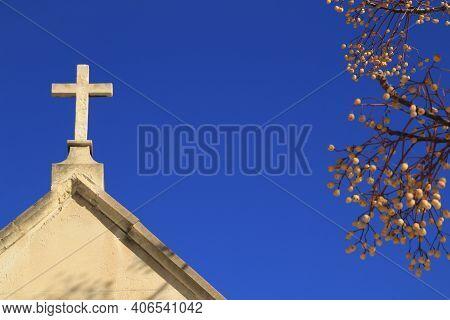 Cemetery Stone Cross Under Blue Sky In Spain