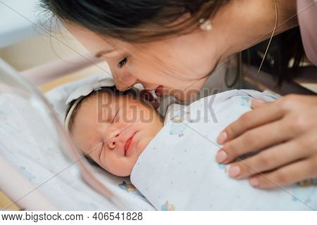 The Mother Leaned Over The Face Of The Newborn Baby In The Cradle