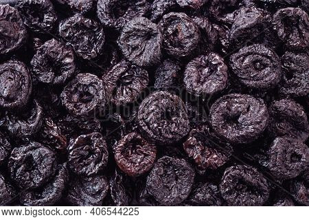 Whole dried plums, pitted. Background of dried plums or prunes fruit.