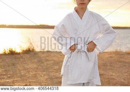 Cute Little Girl In Kimono Near River At Sunset, Closeup. Karate Practicing