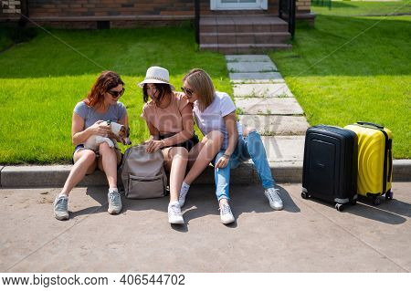 Three Caucasian Women And A Dog Go On A Trip. The Girls Are Sitting On The Curb With Suitcases And W